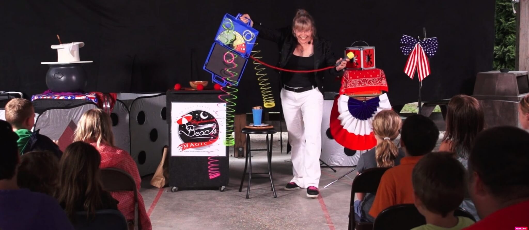 Magician Stephanie Beach performs for a crowd at a local campground.