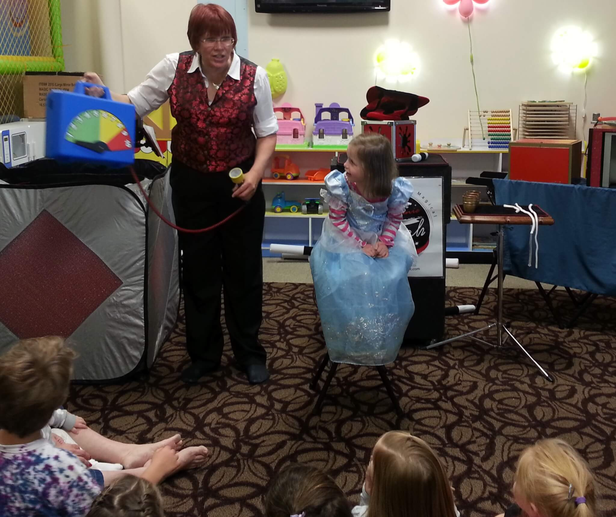 A young girl in a princess dress looks on as children's magician Stephanie Beach performs a birthday magic show.