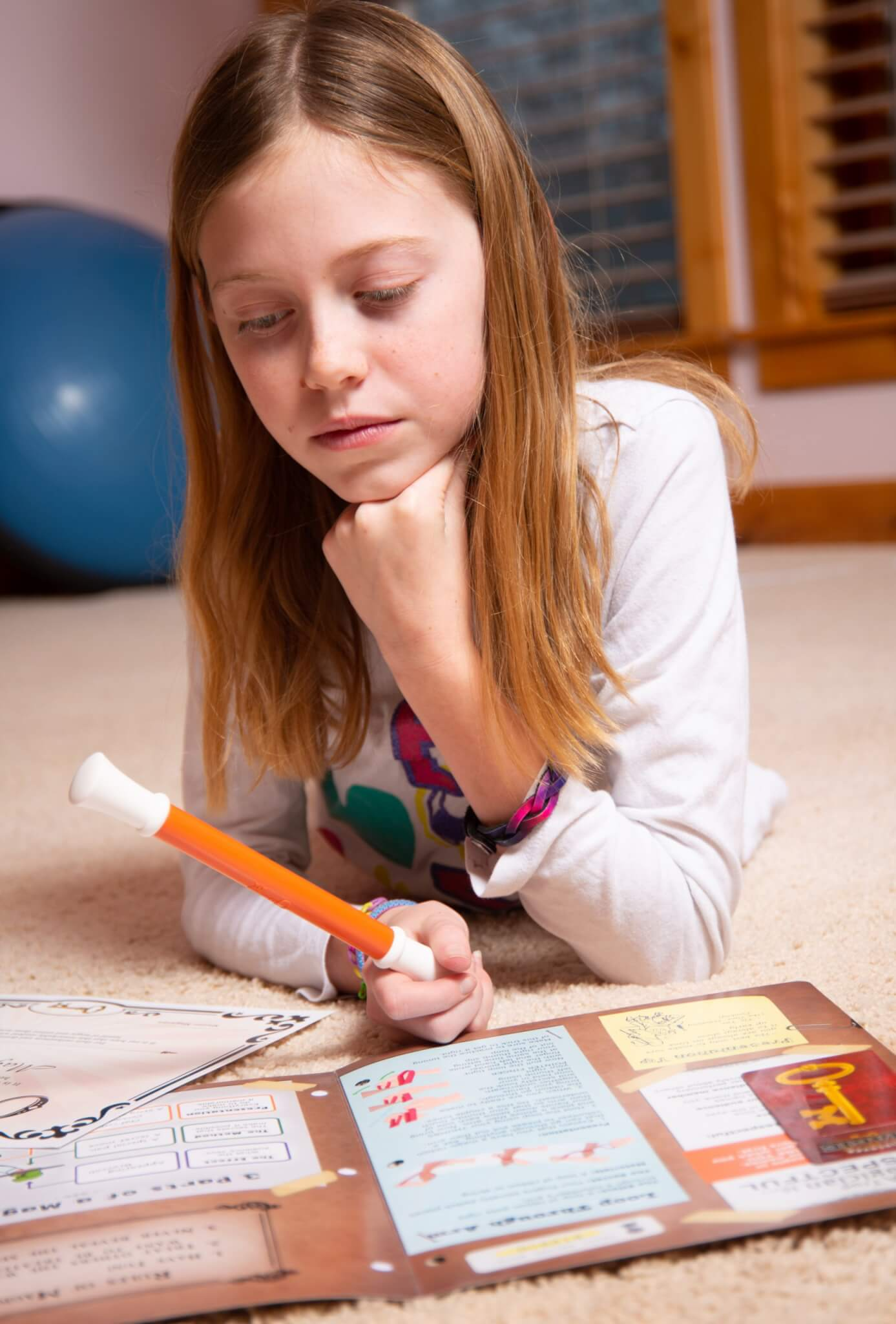 Young girl on the floor with magic kit.