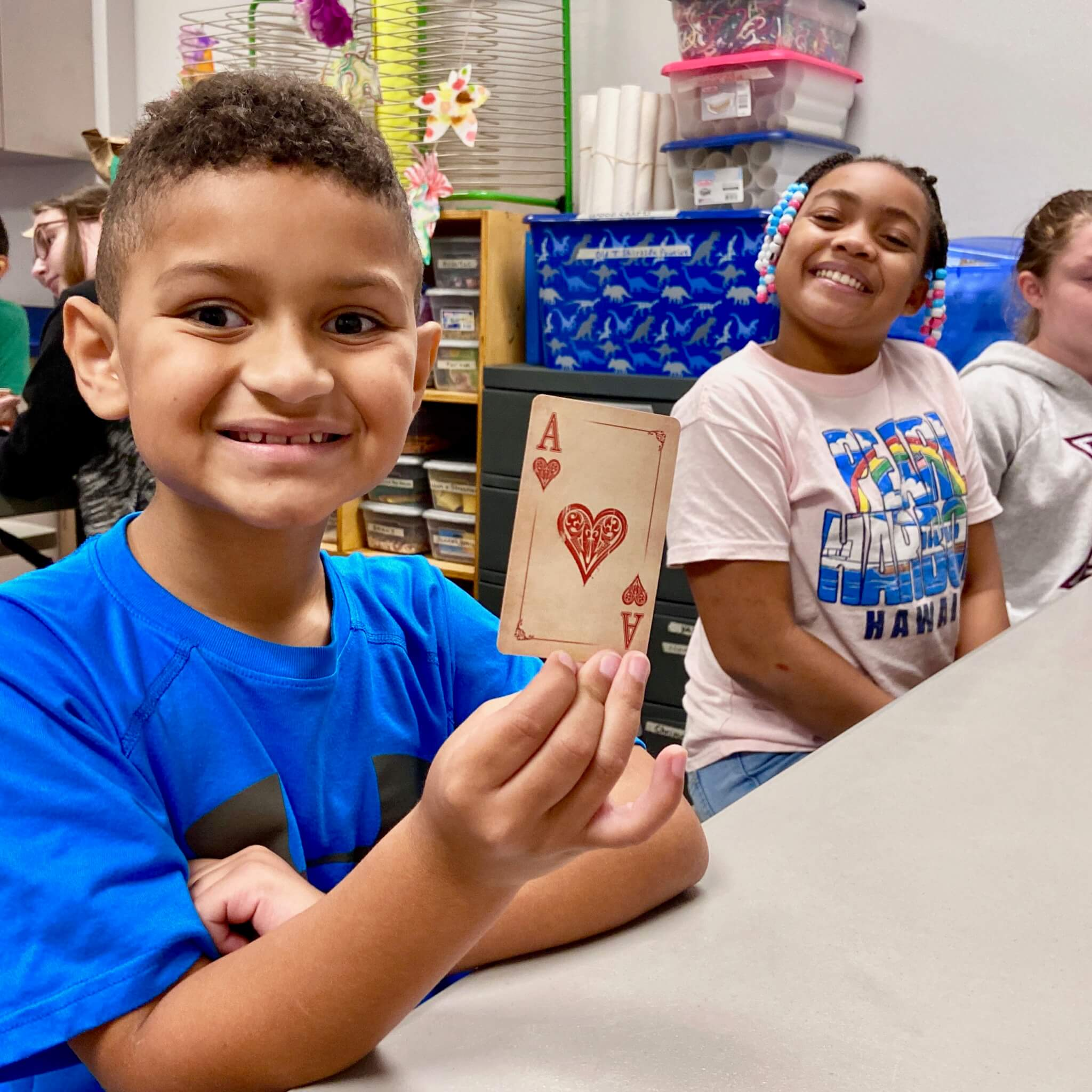 Boy smiling at magic class holding up a card.