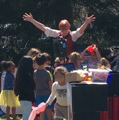 Stephanie Beach surrounded by children during a birthday party magic show.