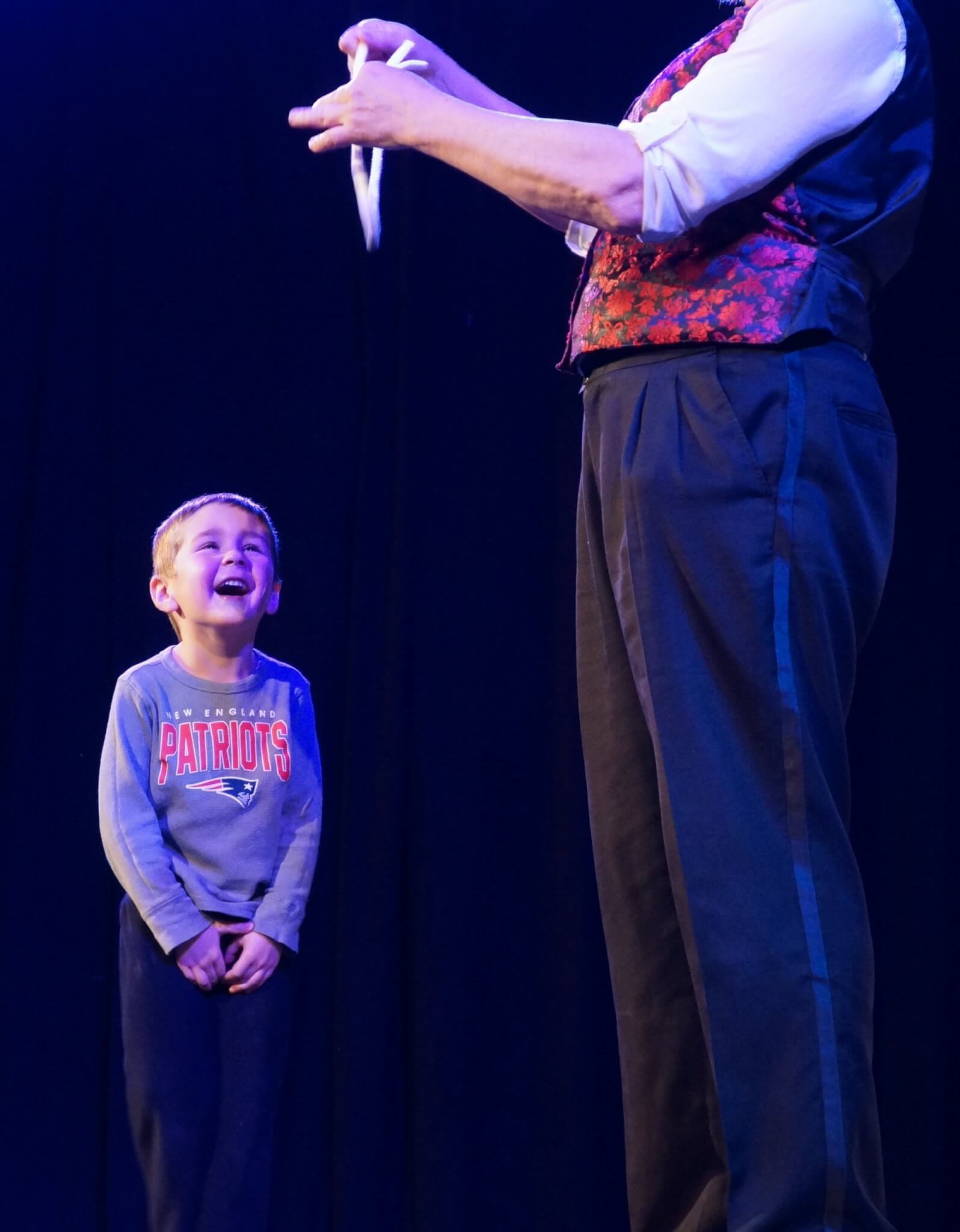 Child looking up at magician Stephanie Beach in amazement.