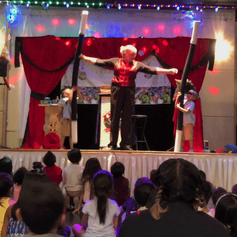 Magician Stephanie Beach on stage during a crowded childrens magic show.