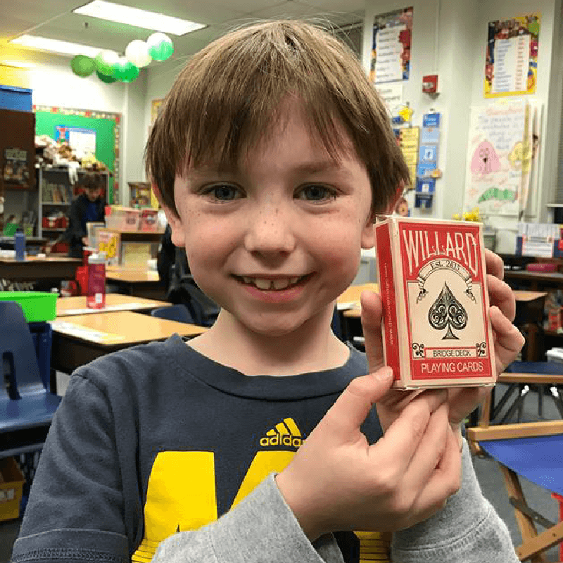 Boy smiling with deck of cards.